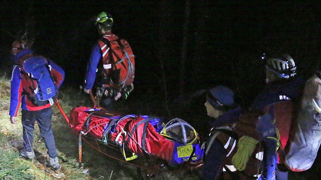 Bergwachthelfer bringen den schwerverletzten Jäger im Steinbachtal zum Rettungsfahrzeug.