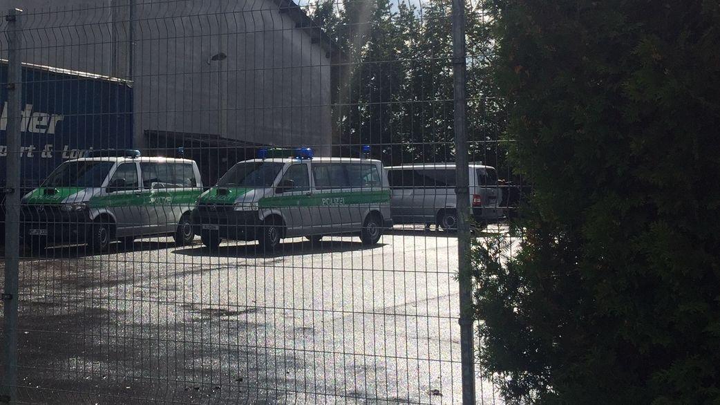 Drei Polizeibusse vor einer Lagerhalle