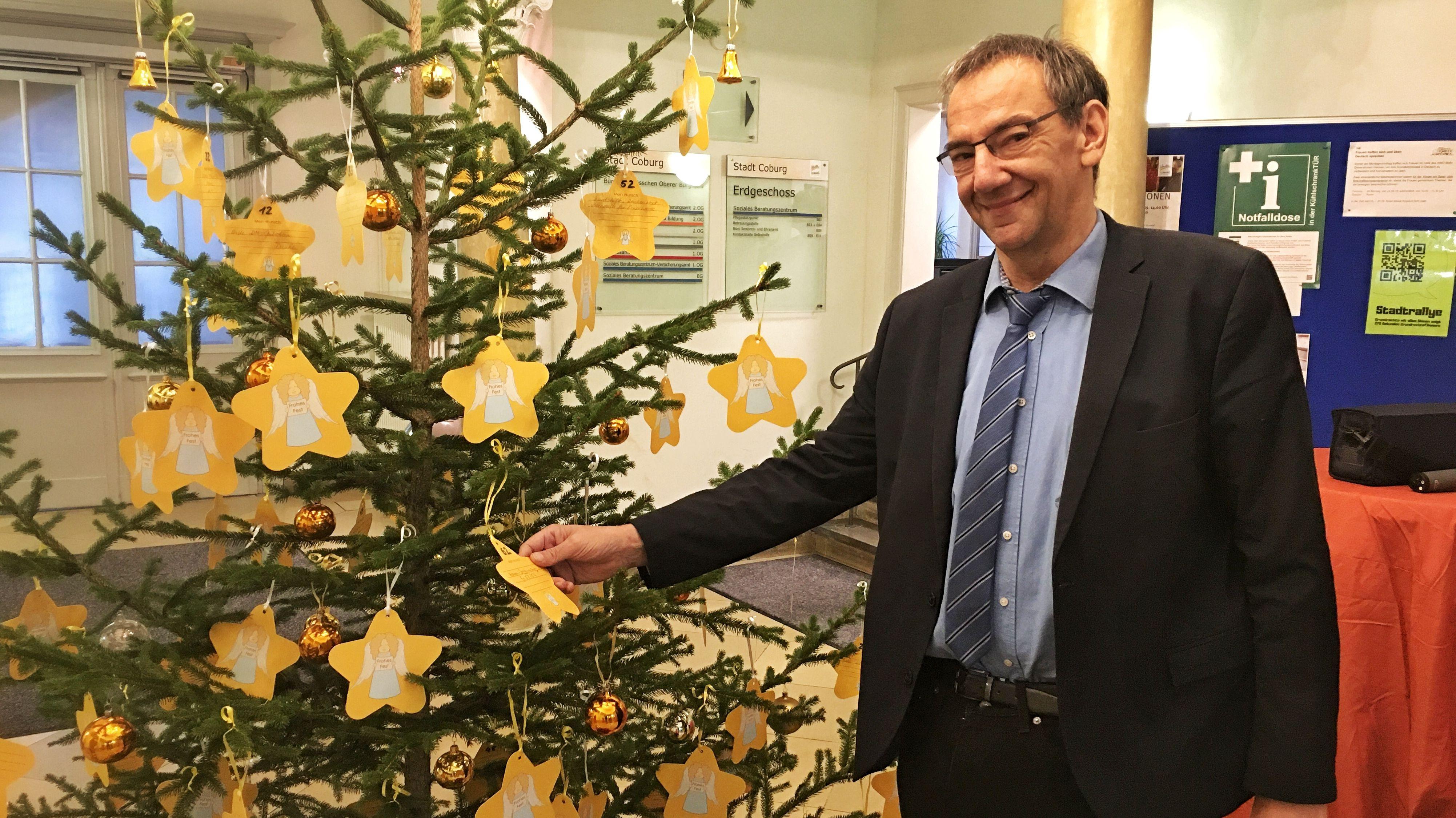 Ein Weihnachtsbaum mit gelben Karten, auf denen Senioren ihre Wünsche schreiben können, daneben der Leiter des Sozialreferats der Stadt Coburg, Thomas Nowak.
