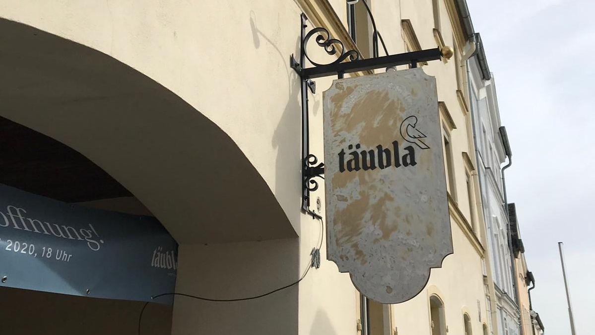 """Ein Schild mit der Aufschrift """"täubla"""" hängt an einer Hausfassade"""