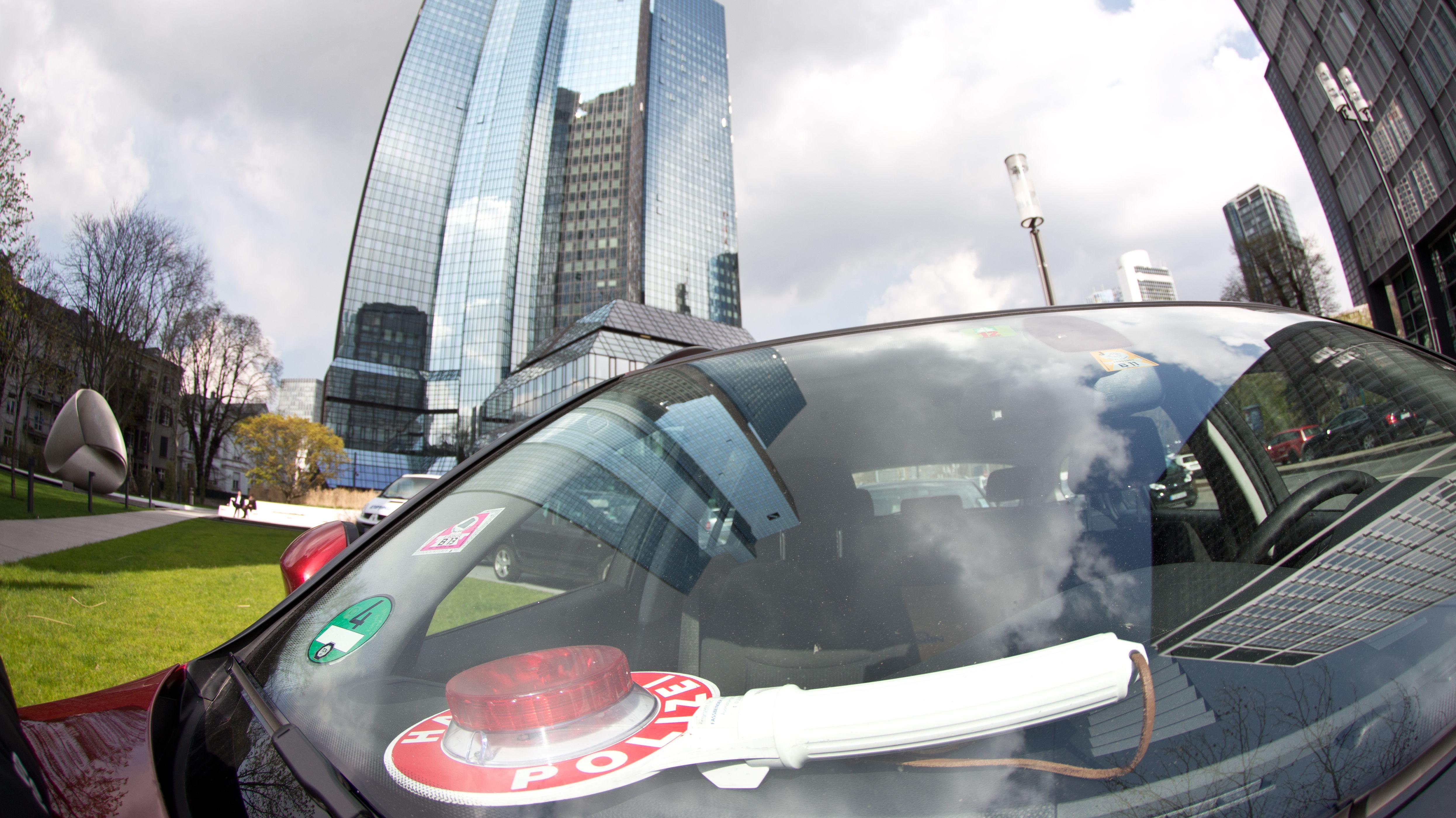 Ein Zivilfahrzeug der Polizei vor der Zentrale der Deutschen Bank