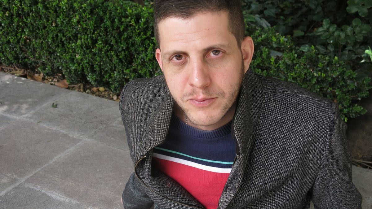 Ein junger Mann sitzt am Boden und blickt in die Kamera