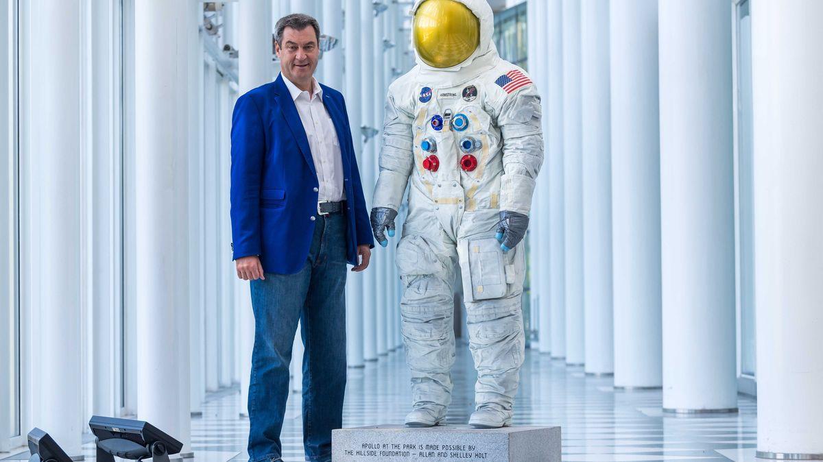 Markus Söder (CSU), Ministerpräsident von Bayern, steht neben einem 3D-Scan des Raumanzugs von Neil Armstrong