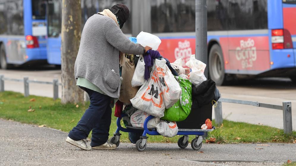 Eine obdachlose Frau schiebt ihre Habseligkeiten in Plastiktüten verpackt in einem Einkaufswagen durch München.   Bild:picture alliance / SvenSimon