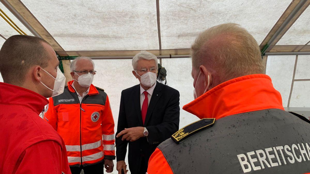 BRK-Präsident Zellner (schwarzer Anzug) im Gespräch mit den BRK-Mitarbeitern an der Teststation