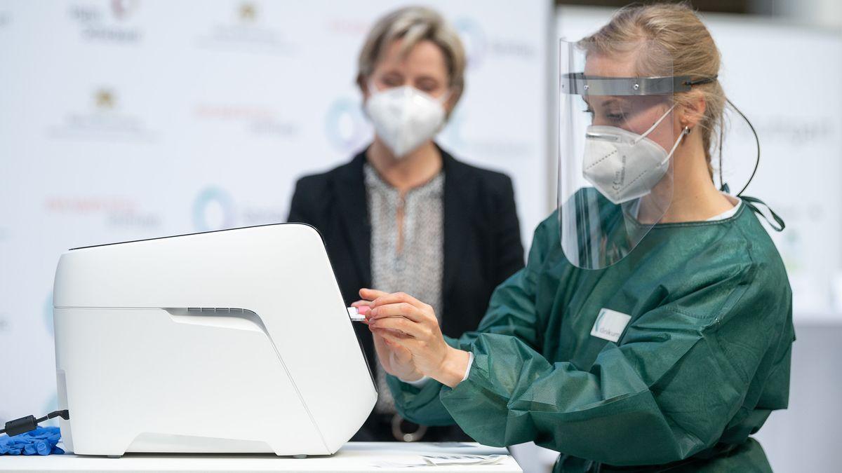 Eine Ärztin führt während der Vorstellung des PCR Corona-Schnelltests Rhonda  eine Kartusche mit dem Teststäbchen in das Testgerät ein.