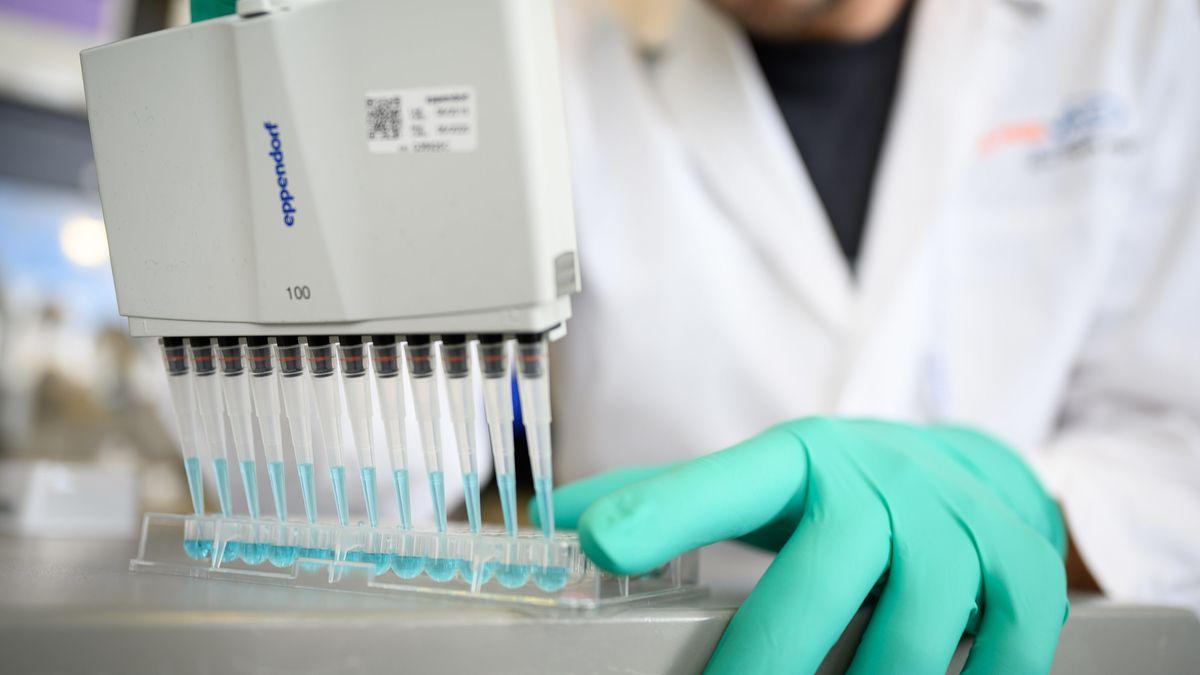 Ein Mann pipettiert in einem Labor eine blaue Flüssigkeit.