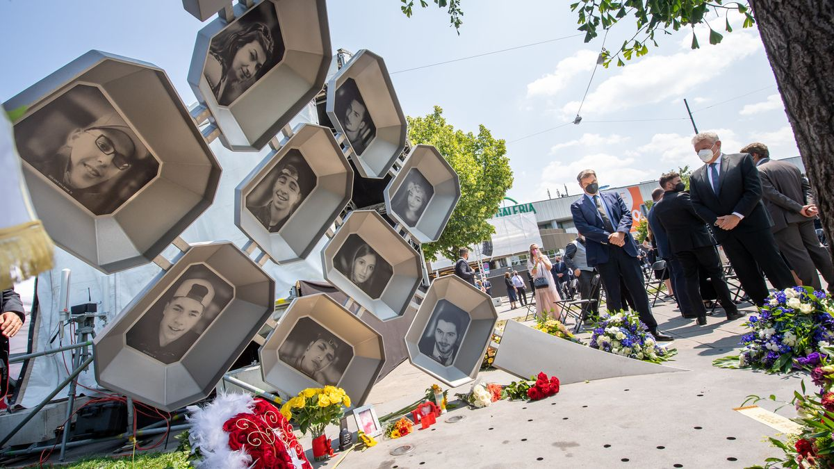 Im Vordergrund das Mahnmal für die Opfer des Attentats am OEZ mit den Fotos der Getöteten, im Hintergrund Ministerpräsident Markus Söder und Münchens Oberbürgermeister Dieter Reiter.