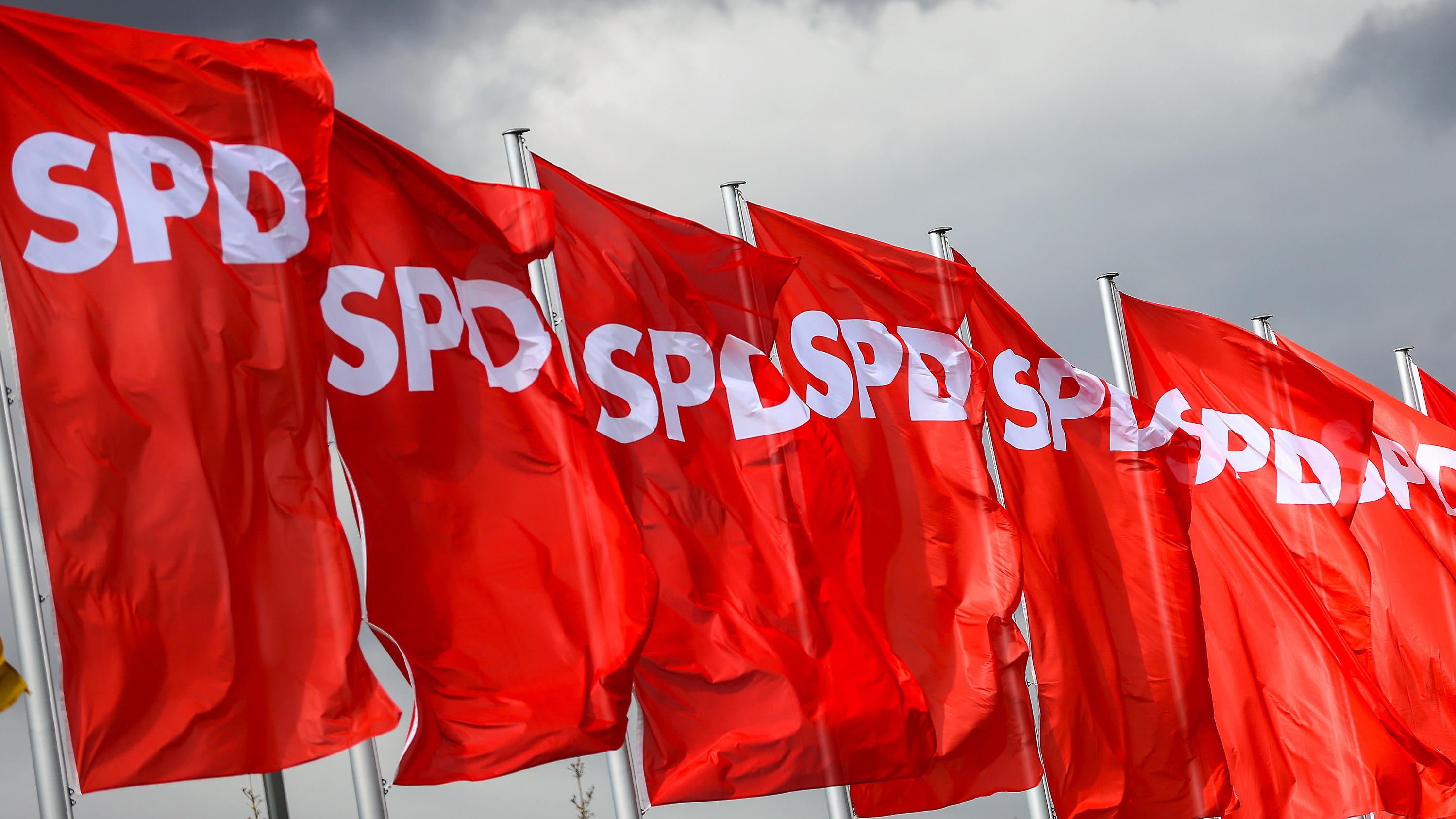 SPD-Fahnen wehen vor dunklen Wolken