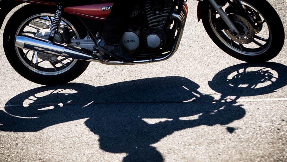 Motorrad und Fahrer werfen Schatten auf den Asphalt.