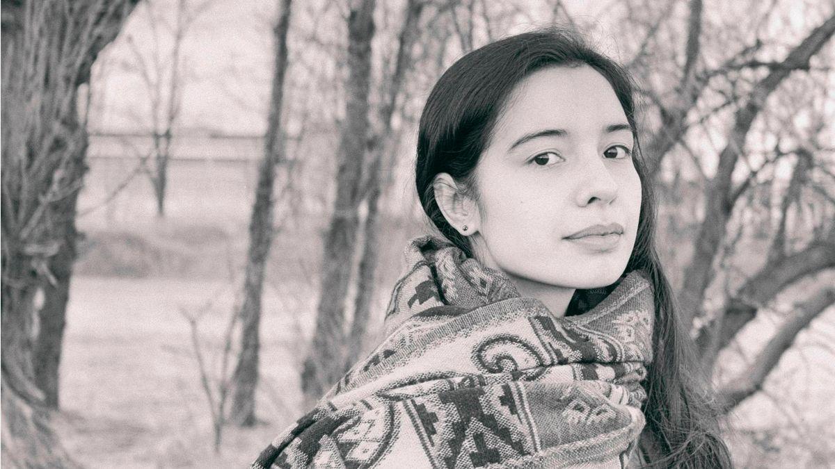 Junge Frau mit langen dunklen Haaren und eingehüllt in einen dicken Schal steht zwischen Bäumen und sieht den Betrachter an