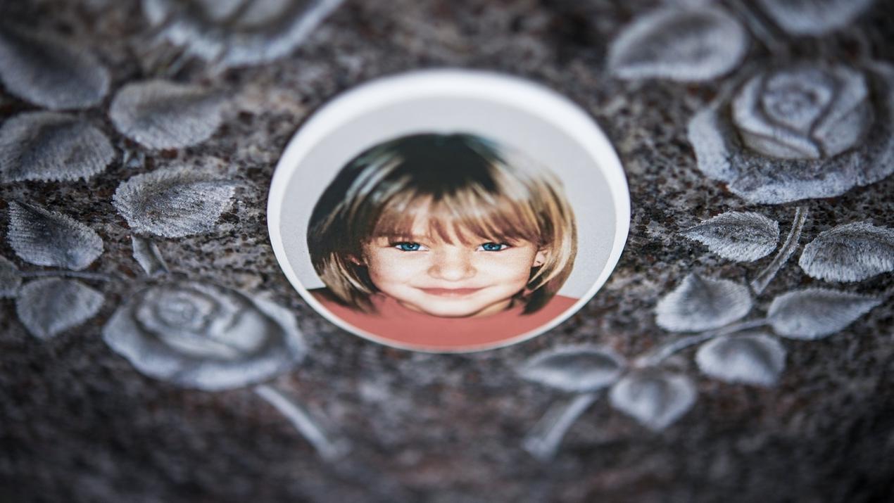 Ein Gedenkstein mit dem Porträt des Mädchens Peggy auf dem Friedhof