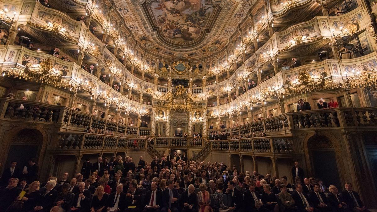 Das Markgräfliche Opernhaus von innen. Im Zuschauerraum sitzen viele Menschen in Abendgarderobe.