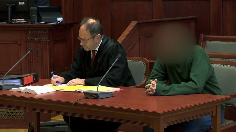 Der mutmaßliche Messerstecher im grünen Pullover sitzt neben seinem Anwalt auf der Anklagebank des Landgerichts.