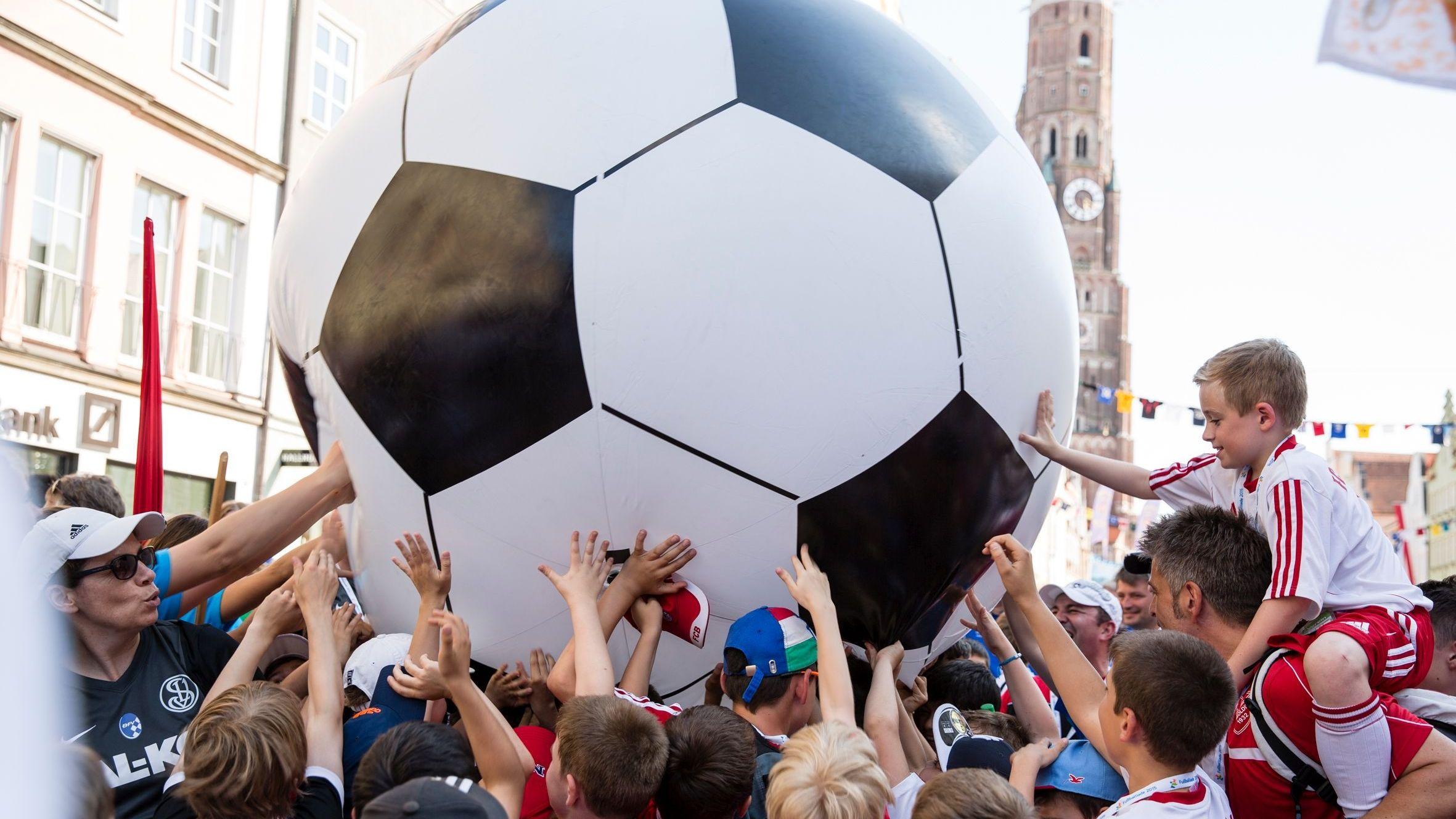 Kinder halten in der Landshuter Fußgängerzone einen überdimensionalen Fußball hoch
