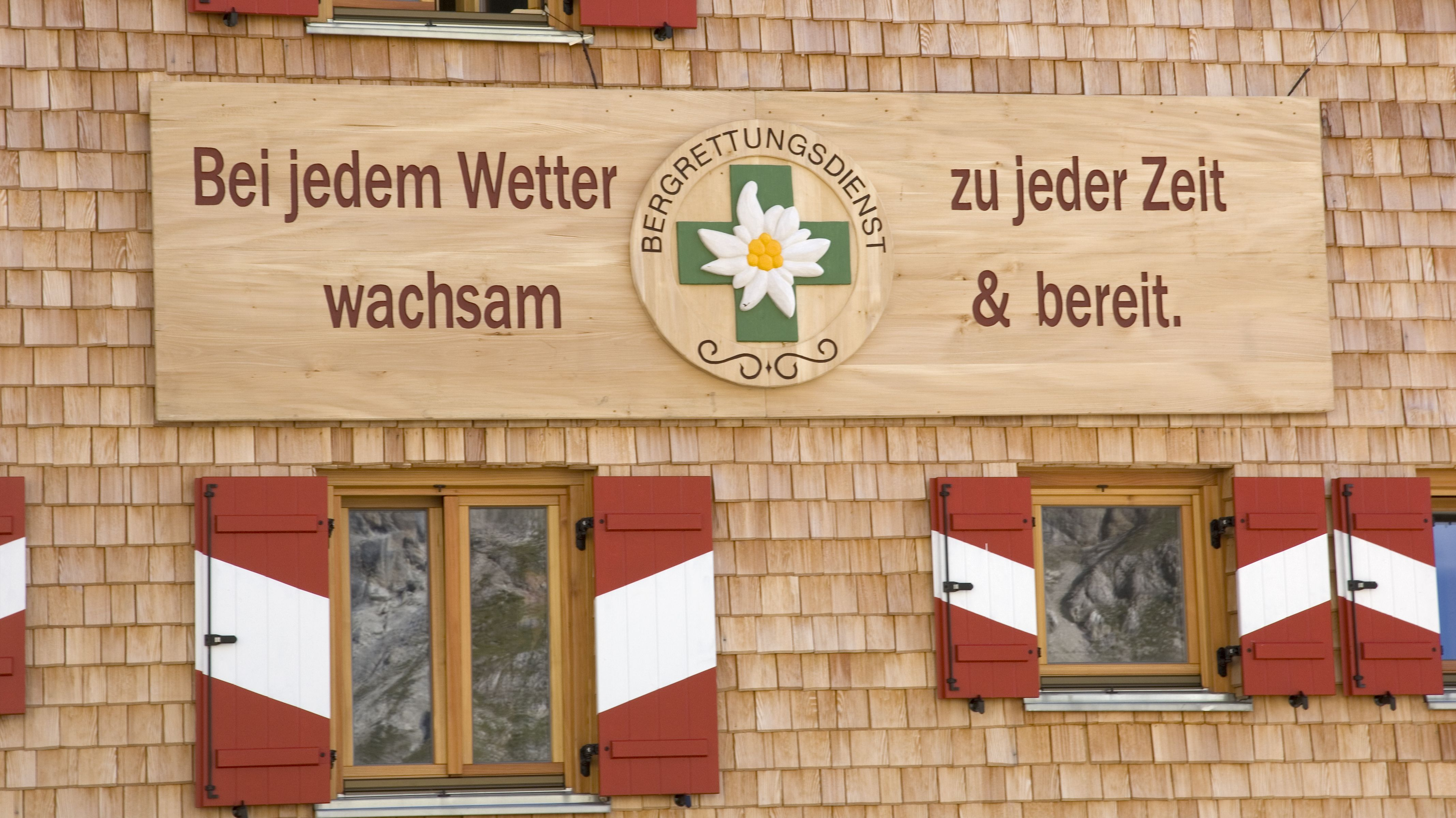 Bergwacht-Schild an einer Hütte in Österreich: Bei jedem Wetter, zu jeder Zeit wachsam und bereit