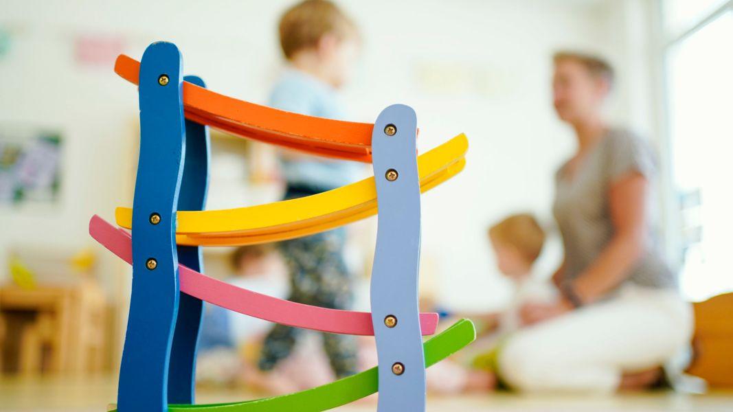 Eine Erzieherin spielt in einer Kindertagesstätte hinter einer Rollbahn mit Kindern.