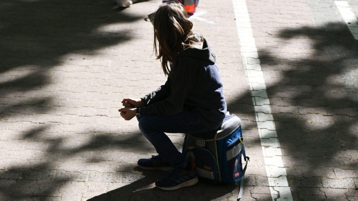 Ein Mädchen sitzt alleine auf ihrem Schulranzen (Symbolbild)