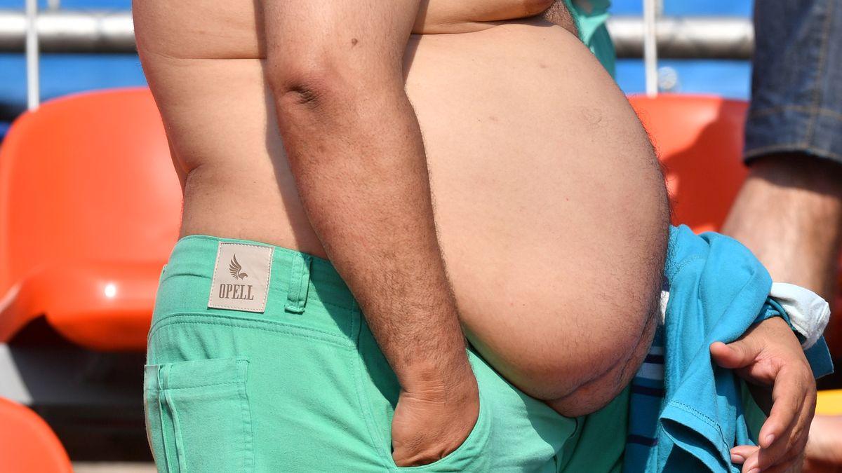 Mann ohne Hemd präsentiert seinen dicken Bauch.