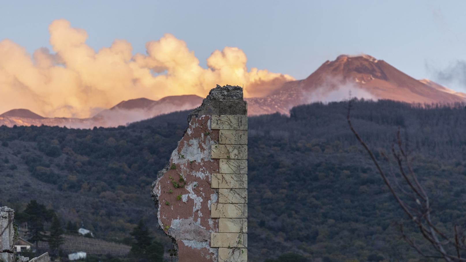 Hinter den Überresten eines eingestürzten Gebäudes steigen Rauchfahnen auf aus dem Vulkan Ätna in Fleri, Sizilien.