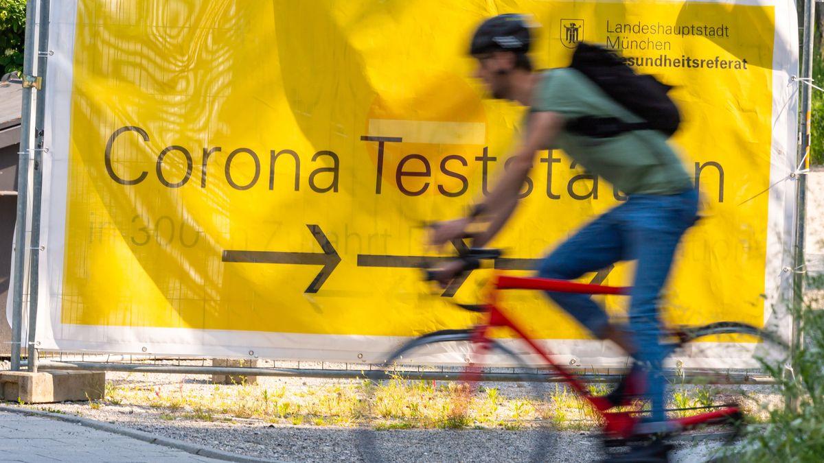 Ein Fahrradfahrer passiert eine große Plane mit der Aufschrift ·Corona-Teststation·.
