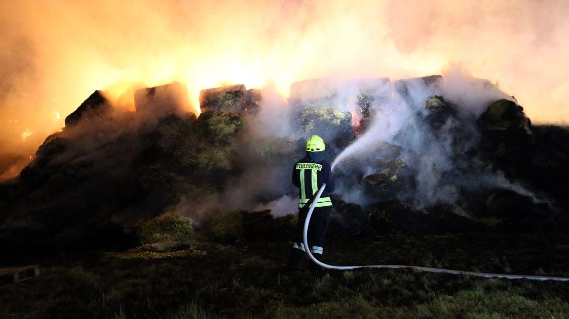Feuerwehrmann löscht Stroh- und Heuballenbrand