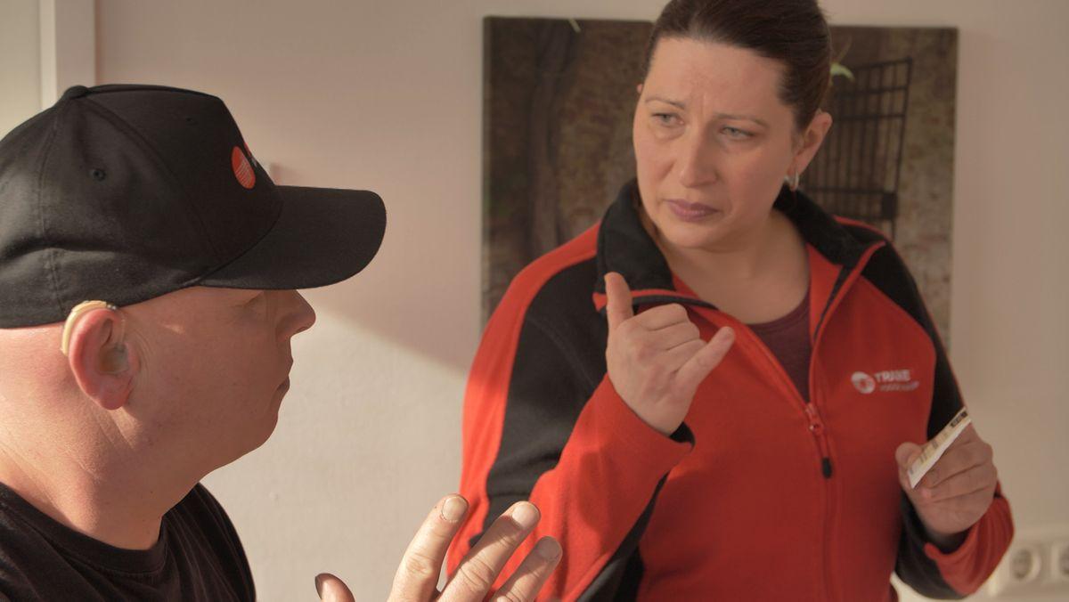 Ein Mann mit Hörgerät und eine Frau sprechen in Gebärdensprache miteinander.