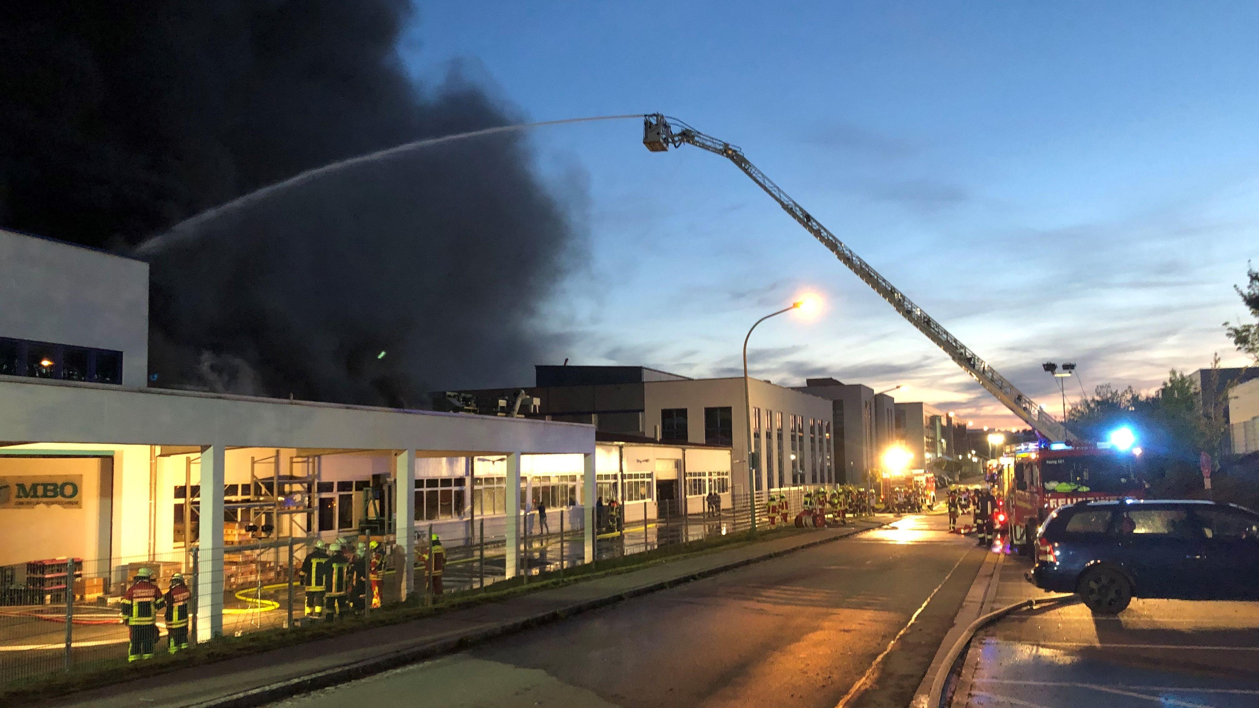 Die Feuerwehr löscht von einer Drehleiter aus die Industriehalle in Roding