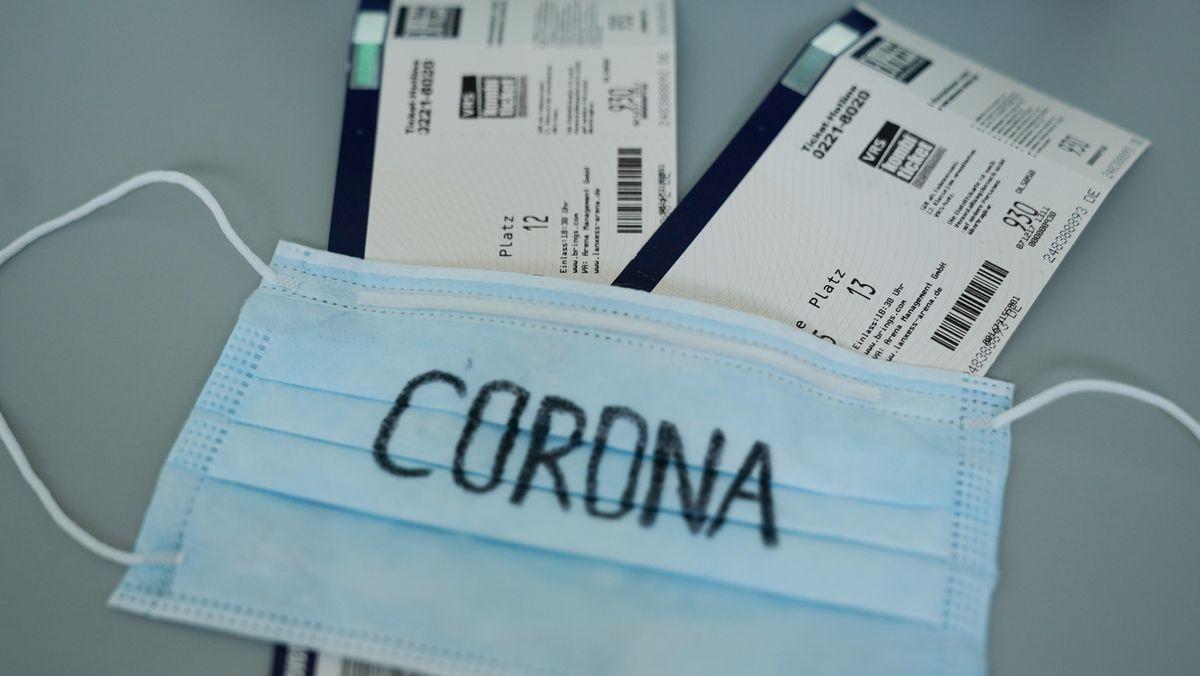 """Maske mit der Aufschrift """"Corona"""" liegt auf zwei Eintrittskarten"""