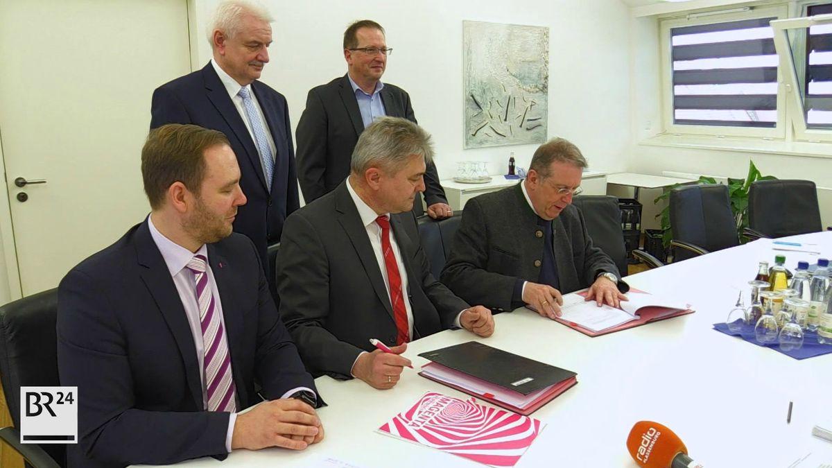 Der Kulmbacher Oberbürgermeister Henry Schramm (rechts im Bild) sitzt mit Vertretern der Telekom an einem Tisch, mit denen er einen Vertrag über den Breitband-Ausbau unterschreibt.