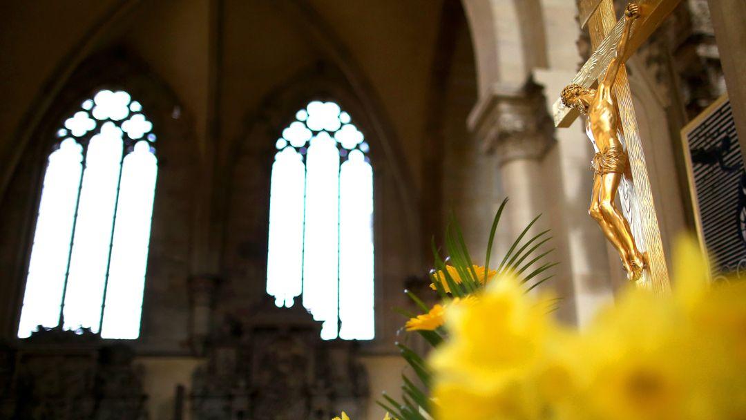 Ein Jesuskreuz und ein Strauß Osterglocken stehen im Dom zu Magdeburg Sankt Mauritius und Katharina.