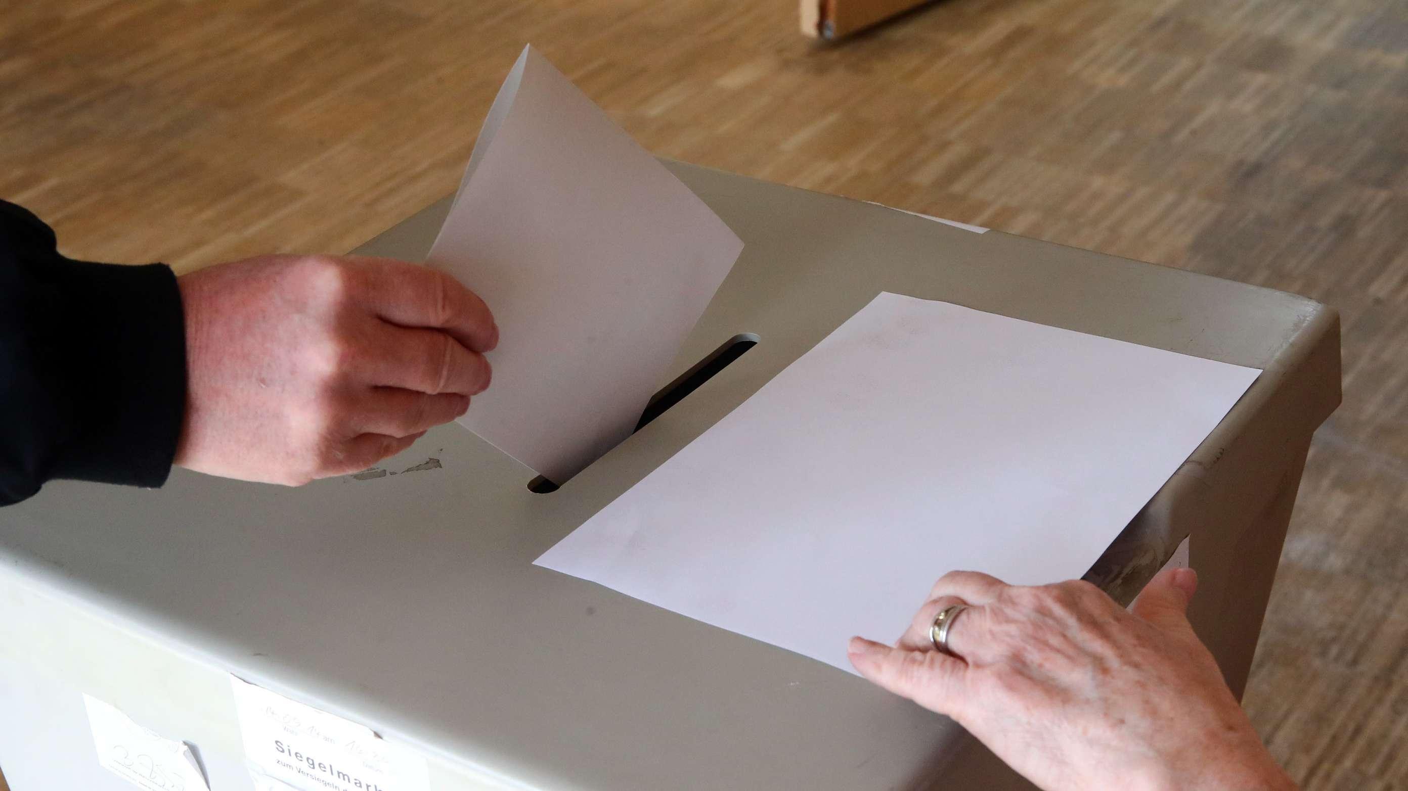 Jemand wirft seinen Wahlschein in die Wahlurne