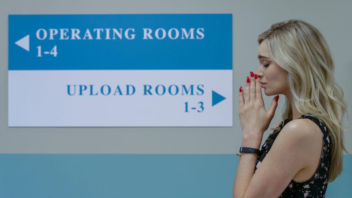 """Im Krankenhaus steht eine Frau vor einem Schild mit der Aufschrift """"OP-Räume"""" links, Upload-Räume rechts."""