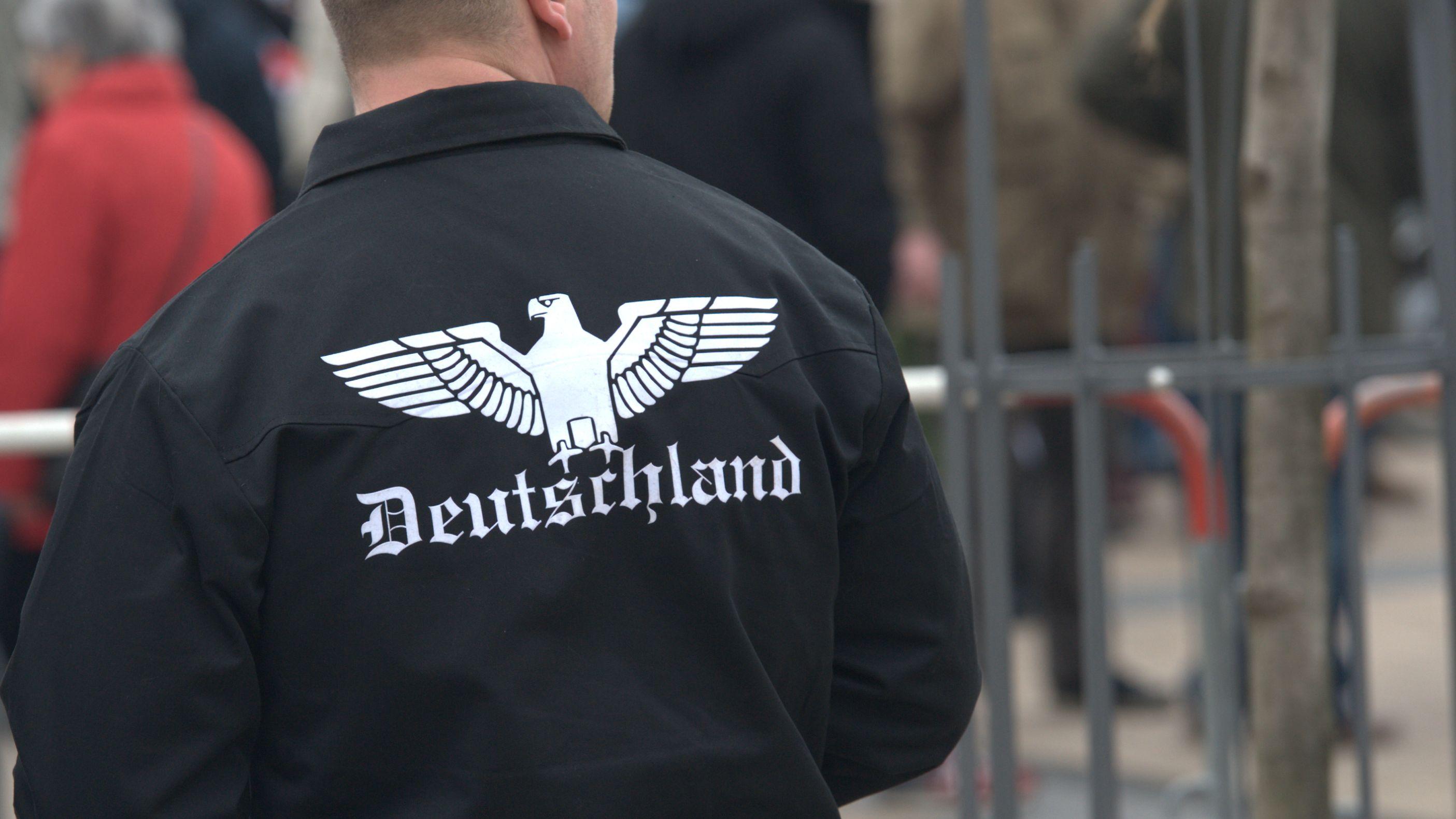 """Schriftzug """"Deutschland"""" auf der Jacke eines Mannes, der an einem Protestzug teilnimmt"""