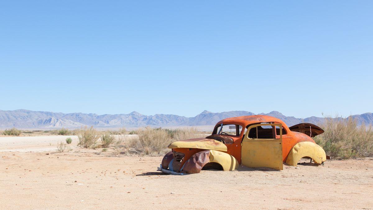 Vor sich hin verrottender VW-Käfer steht mitten in einer Wüstenlandschaft in Afrika.