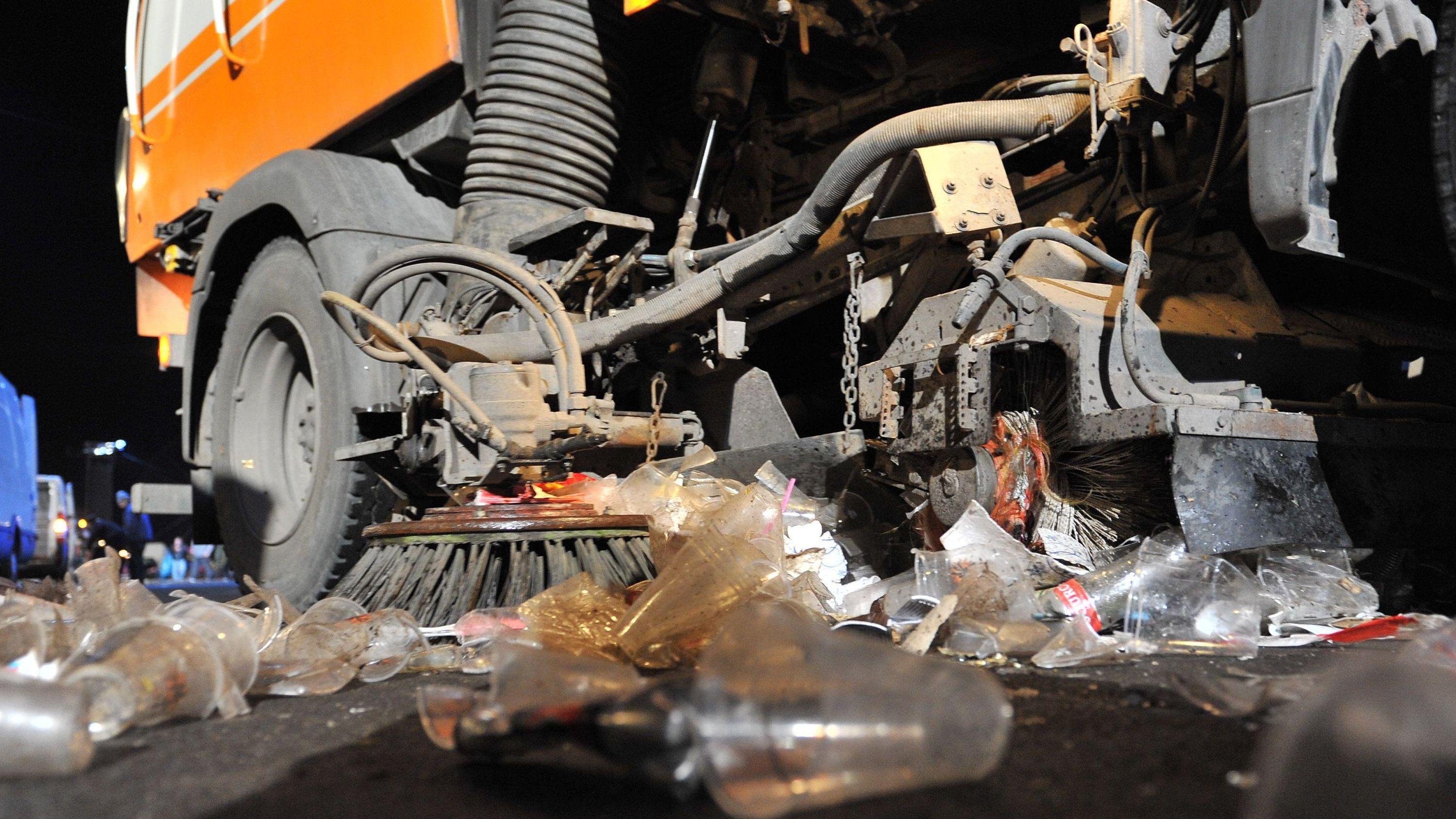 Ein Räumungsfahrzeug beseitigt Müll auf einer Straße am Brandenburger Tor. Hersteller von Wegwerfartikeln sollen in Zukunft die Kosten fürs Sauberhalten von Straßen und Parks mittragen.