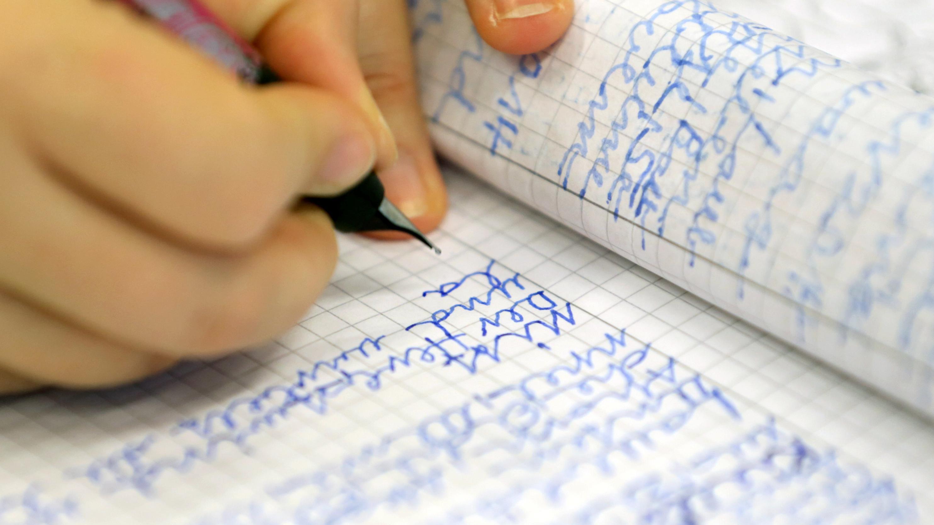 Hand schreibt in kariertes Schreibheft
