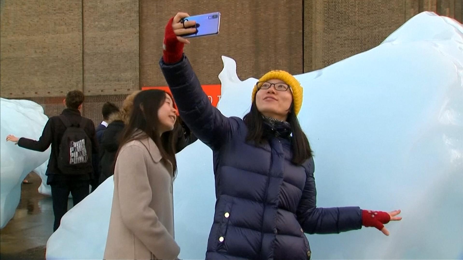 Touristin in London vor schmelzendem Eisberg