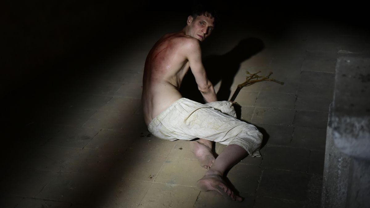 Auf einem Steinboden in einem Keller halb liegender junger Mann, der einen roten Rücken mit Narben von heftigen Schlägen hat.