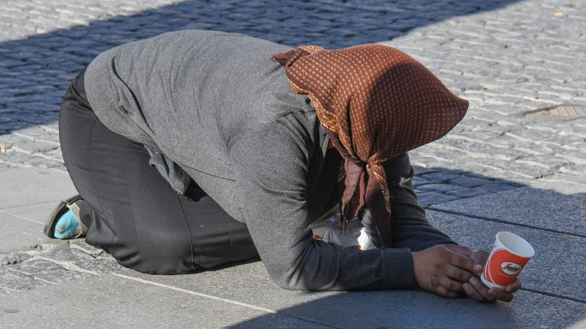 Eine Frau bettelt in Demutshaltung in der Innenstadt in München um ein Almosen.