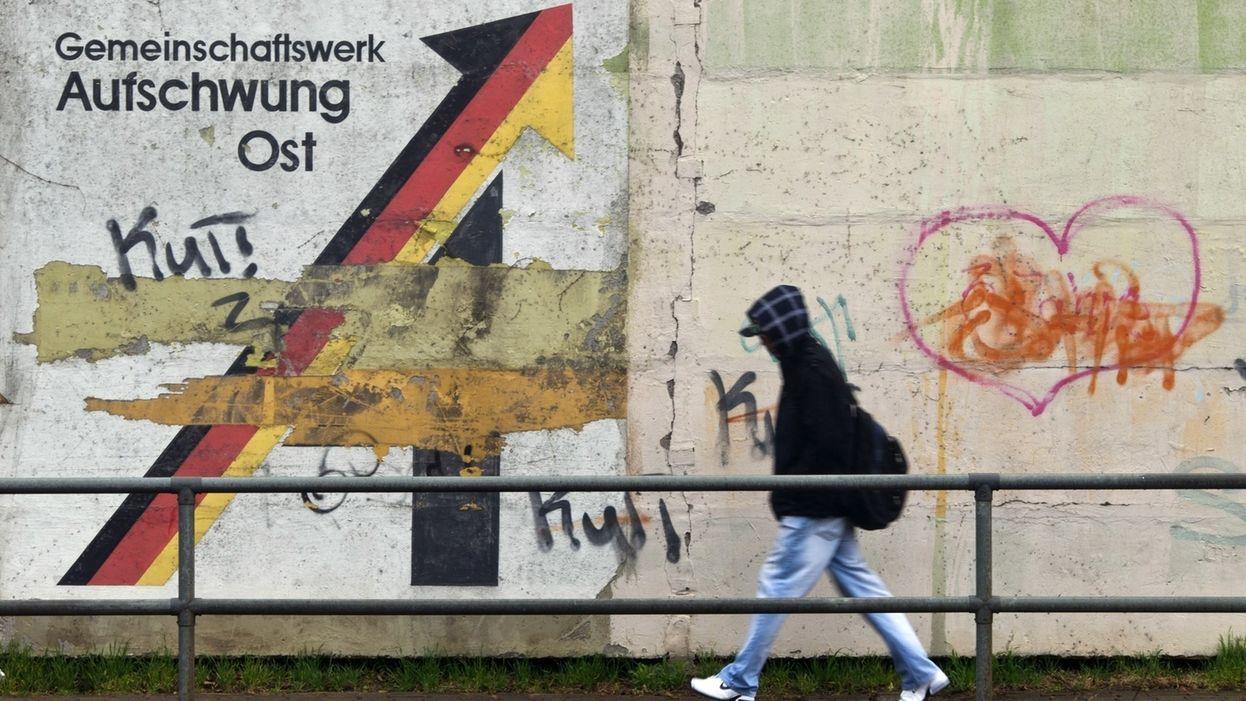Ein Passant geht an einer Schallschutzmauer an einem aus der Wendezeit stammenden verwitterten Wandbild mit dem Schriftzug «Gemeinschaftswerk Aufschwung Ost» vorbei.