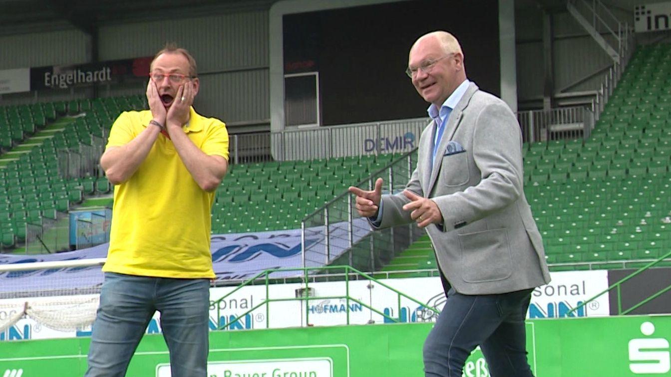 Volker Heißmann und Martin Rassau auf dem Rasen im leeren Stadion am Ronhof in Fürth