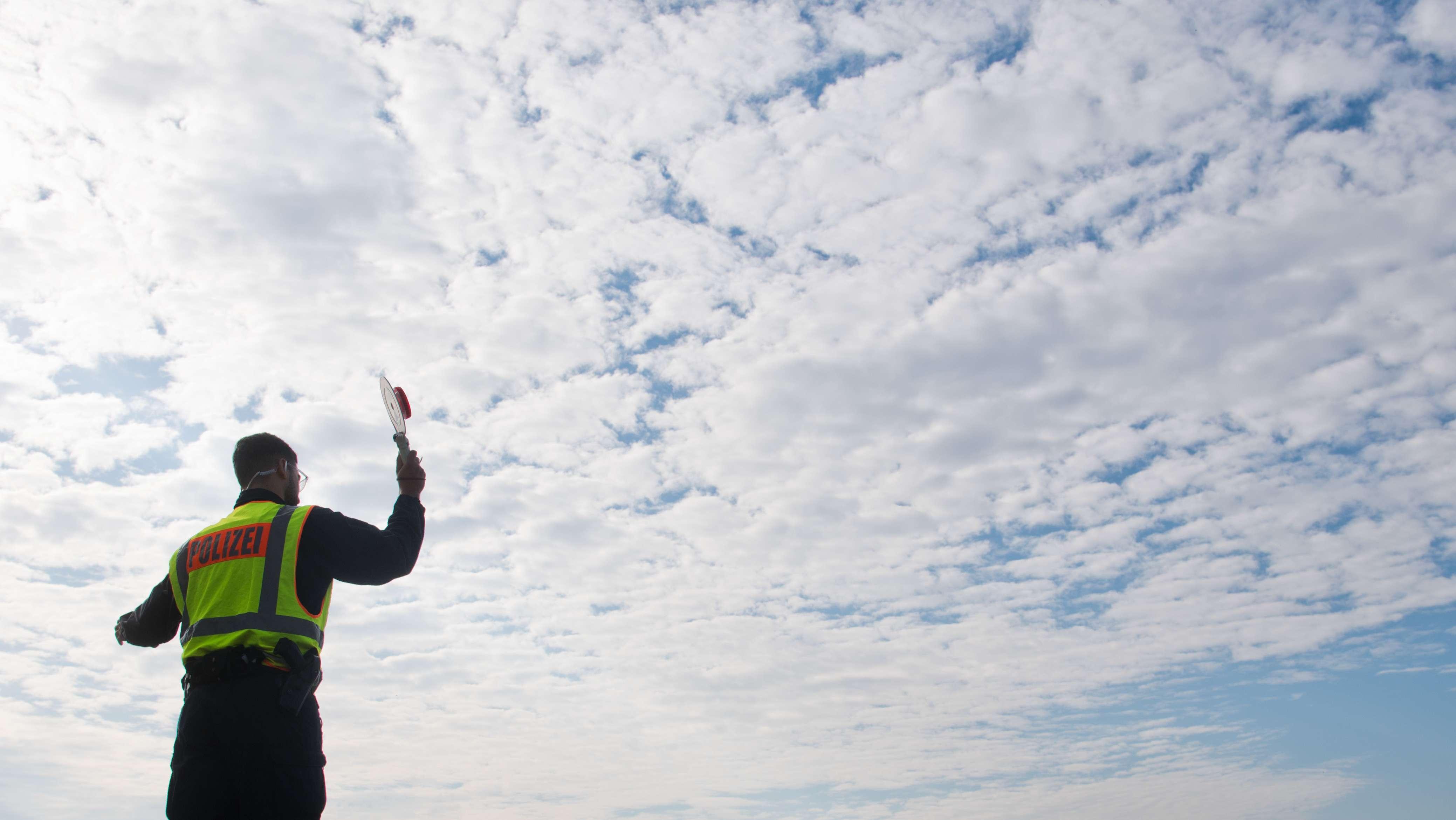 Polizist steht vor wolkenverhangenem Himmel (Symbolbild)