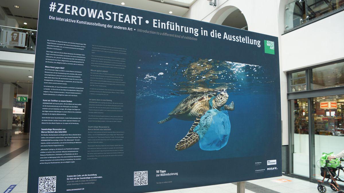 Eine Stellwand zeigt das Bild einer Meeresschildkröte, die sich in einer Plastiktüte verfangen hat.
