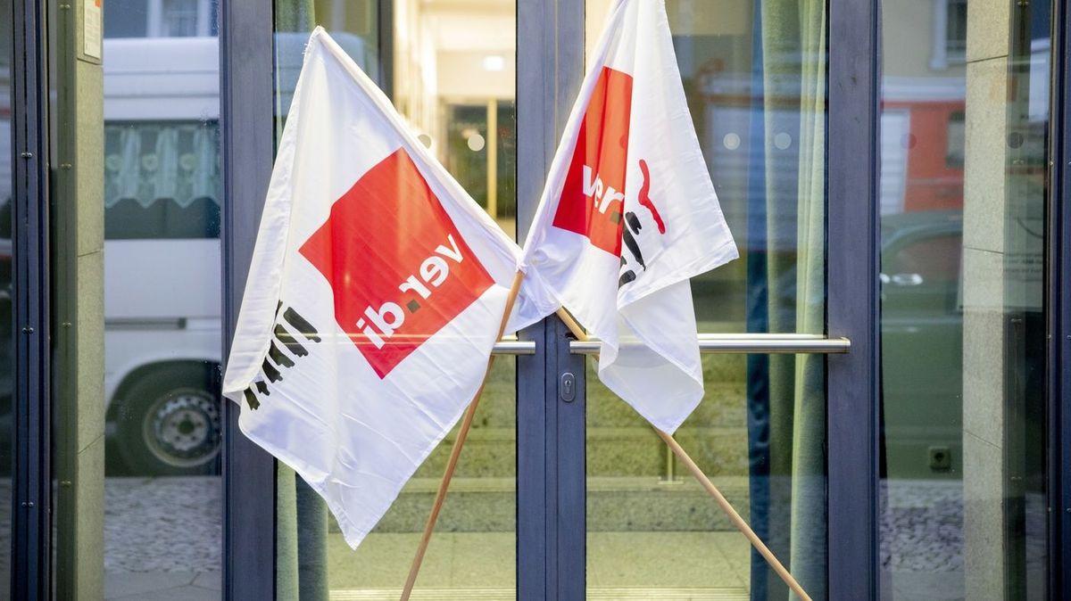 Fahnen der Gewerkschaft Verdi vor einer Tür.