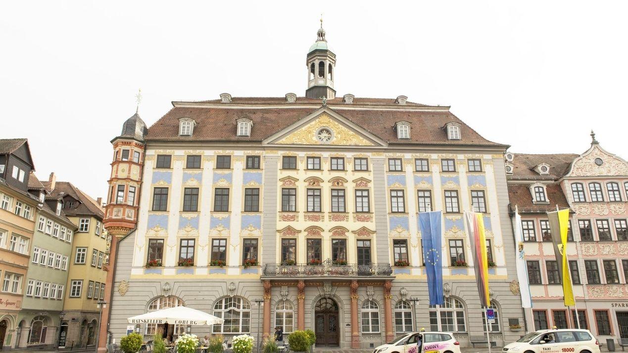 Das Coburger Rathaus, davor Fahnenmasten mit der Europa- und der Deutschlandflagge.