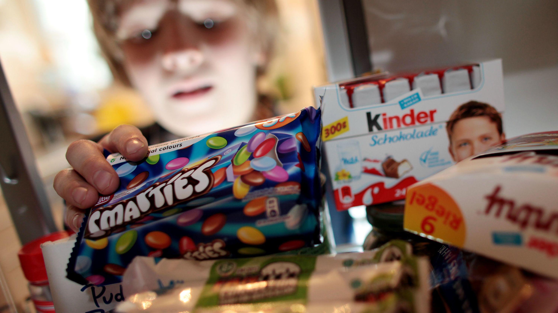 """Archiv: Kind nimmt Süßigkeiten aus einem Schrank - Foodwatch: Am 12.08. ist """"Kinder-Überzuckerungstag"""""""