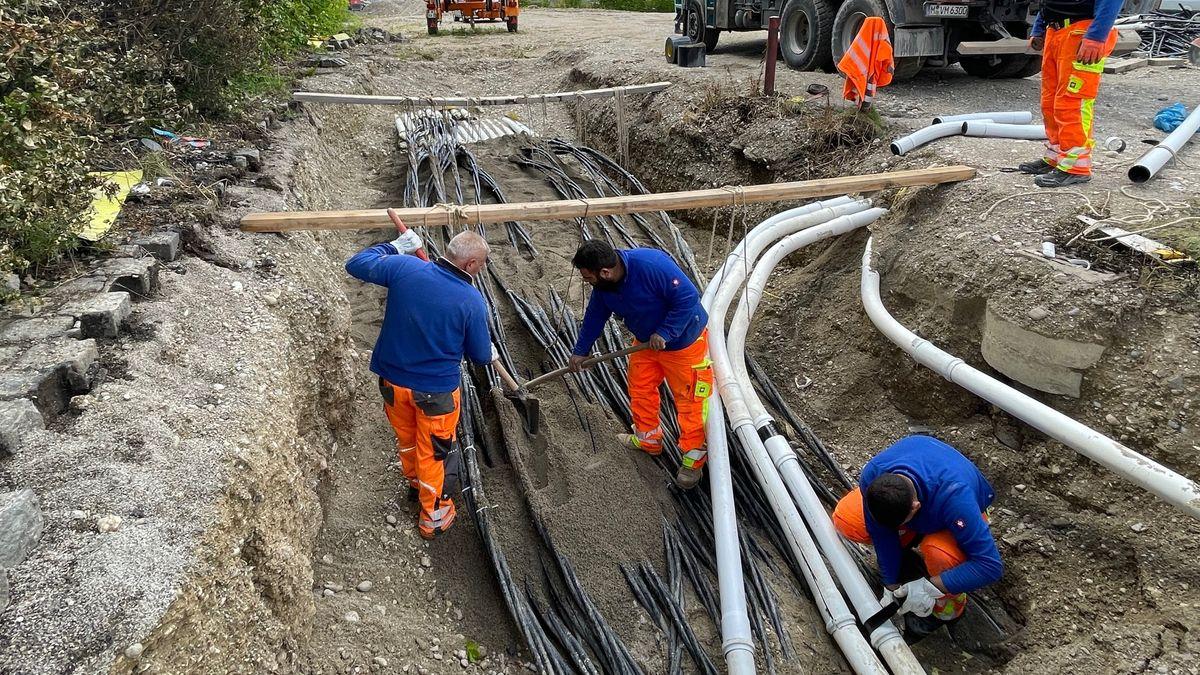 Drei Bauarbeiter stehen in einer Baugrube mit Schaufeln über mehreren Stromkabeln