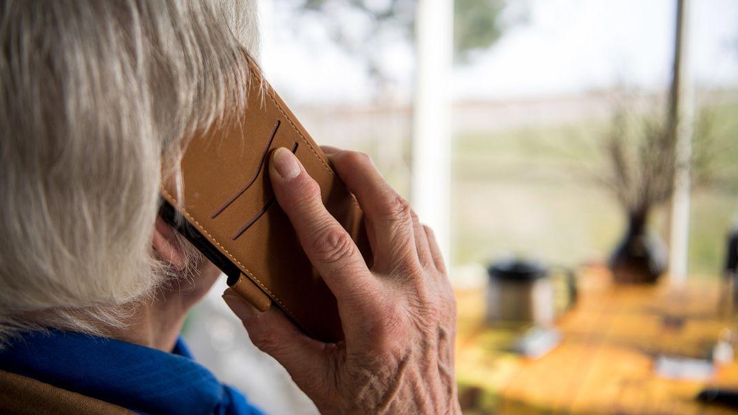 Rentnerin hält Handy ans Ohr.