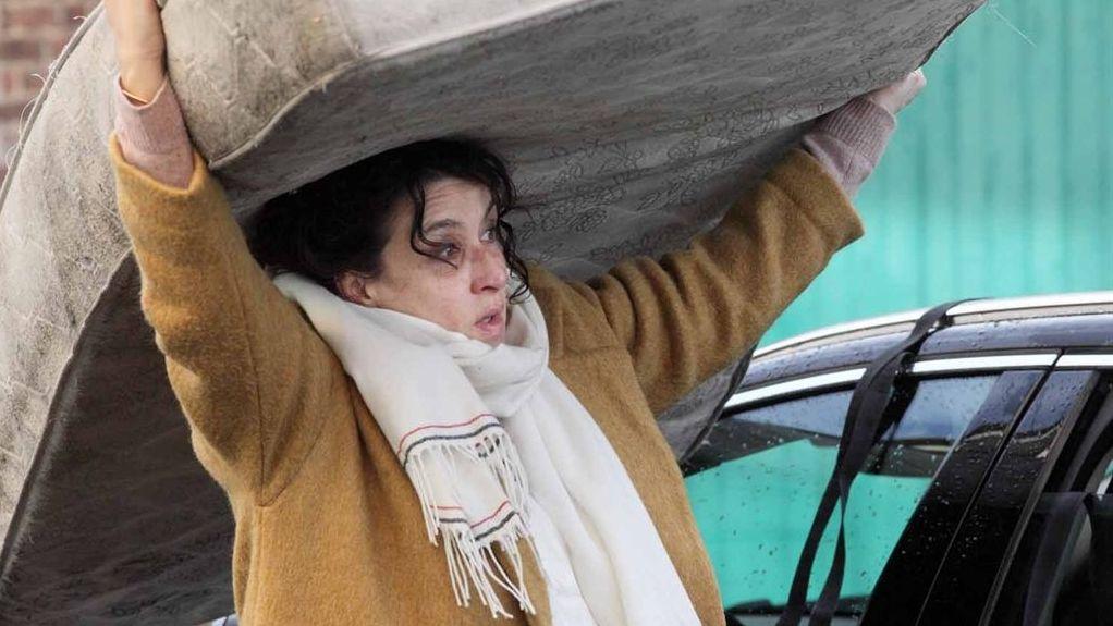 Eine Frau balanciert - auf einer Strasse stehend - eine große Matratze auf ihrem Kopf.